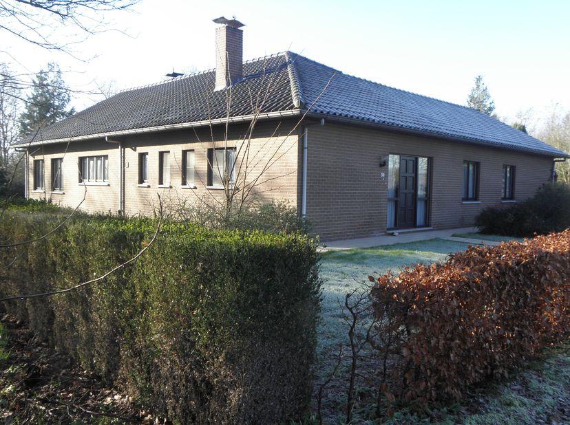 Gelijkvloerse woning met op zuid gerichte tuin, 85are, Gelegen in een rustige omgeving. Woonkamer 55m² in L-vorm voorzien van een schouw en kachel. In